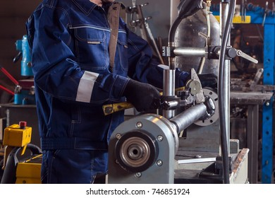Close-up of a male auto mechanic in blue uniform works with a mettalic hammer on an automatic welding machine for the repair of cardan shafts