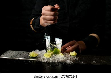 Close-up. Male barman holds black madler in his hand and energetically squeeze slices of citrus to caipirinha cocktail. Pieces of ice and lime at the bar.