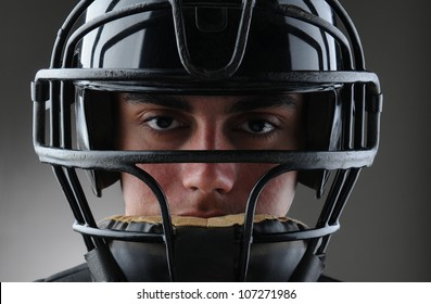 Closeup of a male baseball catcher with his protective mask on. Horizontal format with a light to dark gray background.