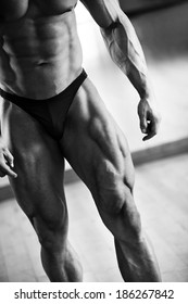 Close-up of male bodybuilder showing his muscular thigh