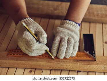 Close-up of male carpenter hands drawing mark on wooden flooring with ruler and pencil. DIY concept.