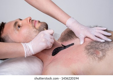 Closeup of male chest with hair and black wax. Professional shugaring master in gloves makes depilation to a young man in the salon