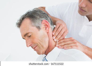 Close-up of a male chiropractor massaging patients neck over white background