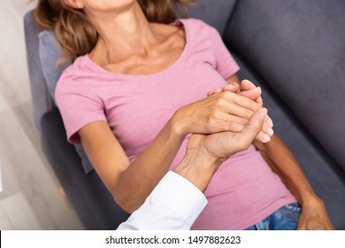 Close-up Of Male Councilor Holding Woman Hand During Hypnotherapy