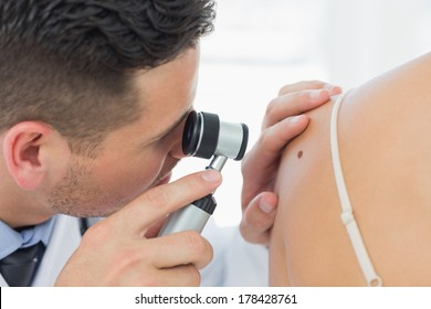 Closeup of male dermatologist checking mole on woman in clinic