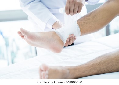 Close-up of male doctor bandaging foot of patient at doctor's office.