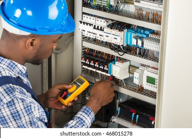 Close-up Of Male Electrician Checking Fuse Box With Multimeter
