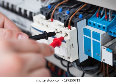 Closeup of male electrician examining fusebox with multimeter probe
