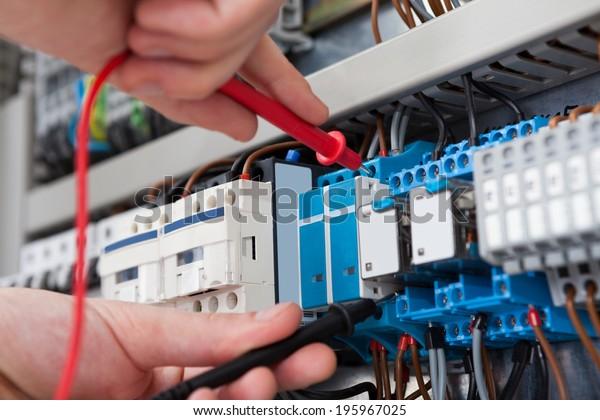 Nahaufnahme eines männlichen Elektrikers, der den Fusebox mit einem Multimeter-Sonde untersucht