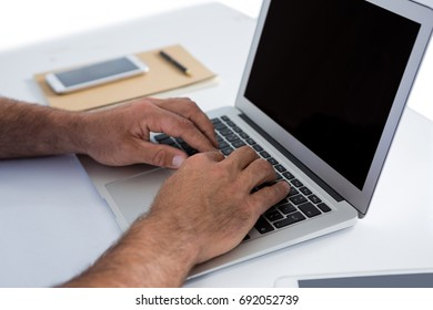 Close-up of male executive using laptop at desk