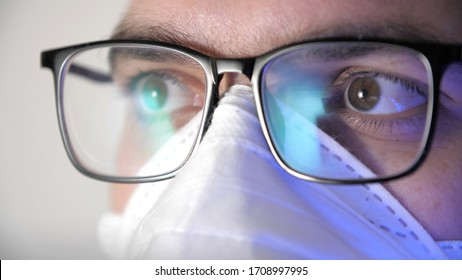 Close-up male face in medical protective mask with glasses. Display reflection in glasses. Portrait of a young man, eyes of programmer with glasses. Work in home. Quarantine