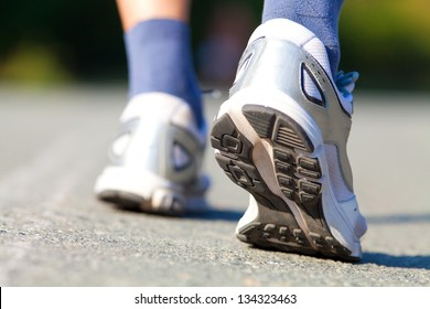 Close-up of male feet in sneakers running outdoors