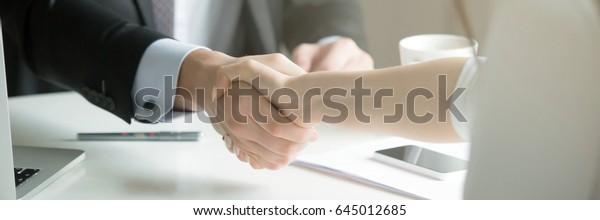 Nahaufnahme von Händen von Männern und Frauen, nachdem wirksame Verhandlungen mit gegenseitigem Respekt geführt haben.Geschäftskonzept. Horizontaler Fotobanner für das Design von Website-Header mit Kopienraum für Text