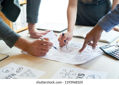 Close-up of male and female hands pointing at financial report with graphs and charts