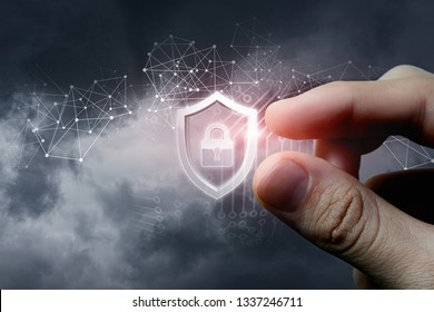 A closeup of male fingers holding digital protection shield with padlock inside surrounded by wireless connections and matrix model. The concept of digital data and information security.
