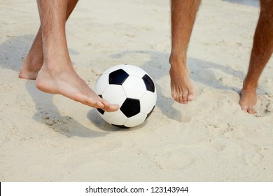 Close-up of male foot playing football on sand