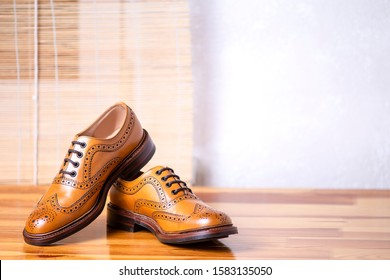 closeup of Male Full Brogued Tan Oxford Shoes. Placed Together on Laqured Table Indoors. Horizontal Image Composirion