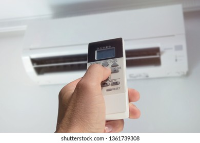 close-up of male hand with air conditioner remote control