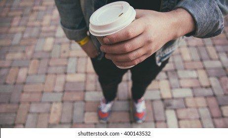 Closeup of male hand with coffee cup on street food festival