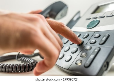 Closeup of male hand dialing a phone number making a business or personal phone call.
