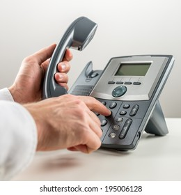 Closeup of male hand dialing telephone number and picking up a handset. Communication concept.
