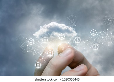 A closeup of a male hand fingers holding a data cloud inside gear and wireless connections mechanism. Data and information and human recourses concept.