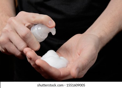 Closeup of a male hand with foam on the palm. man squeezes shaving foam onto his hand. Putting whip foam soap bottle with foam on man hand