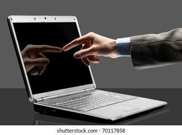 Close-up of male hand with forefinger pointing at laptop screen over black background