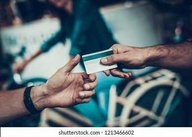 Closeup of Male Hand Gives Credit Card to Seller. Shop Assistant Hand Takes Card with Blurred Customers and White Cycle on Backround in Sport Bicycle Store. Cashless Payments Concept