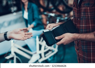 Closeup of Male Hand Gives Money From Purse to Seller. Shop Assistant Hand Takes Cash with Blurred Customers and Bikes on Backround in Sport Bicycle Store. Cash Payments Concept