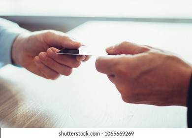 Close-up of male hand giving or passing credit card to another man above table. Unrecognizable businessman paying bill or getting new plastic card in bank. Banking concept