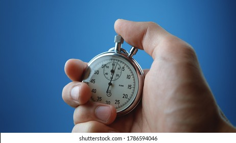 Close-up of male hand holding analogue stopwatch on blue background. Time start with old chronometer man presses start button in the sport concept. Time management concept.