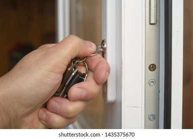 Closeup of a male hand holding a bunch of door keys and locking or opening a door
