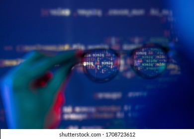 Close-up of male hand holding eyeglasses against computer code, defocused background around glasses