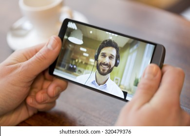 Closeup of a male hand holding his smart phone during a skype video