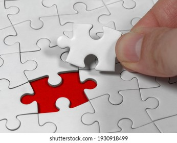 Closeup an male hand holding the jigsaw puzzle solution to the problem missing piece. Concept conceptual metaphor imagine.