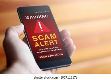 "Closeup of male hand holding modern mobile phone with red screen and warning icon with the text ""SCAM ALERT: This site has been reported as fraudulent. Abort connection"". Concept of internet security."