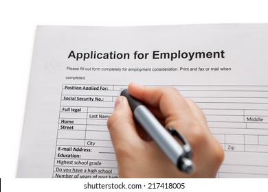 Closeup of a male hand holding a pen completing a job application form in a career and employment concept