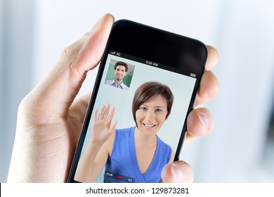 Closeup of a male hand holding a smartphone during a skype video call with his girlfriend or wife