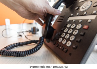 Closeup of male hand holding telephone to make a call using a black landline phone.