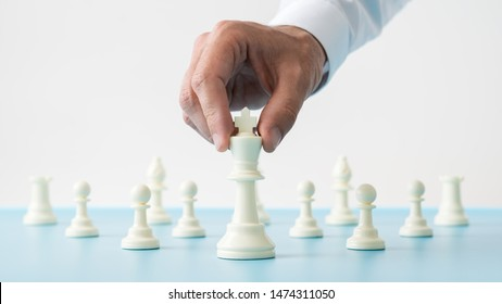 Closeup of male hand holding white chess figure of king positioned in front of the other figures on a blue desk in a conceptual image.