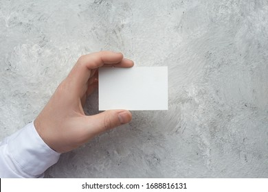 Closeup of male hand holding white business card on concrete wal