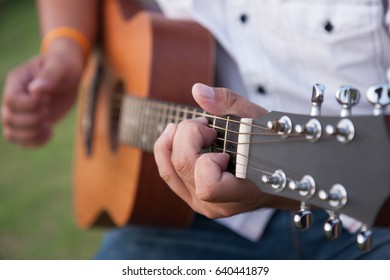 closeup male hand playing acoustic guitar