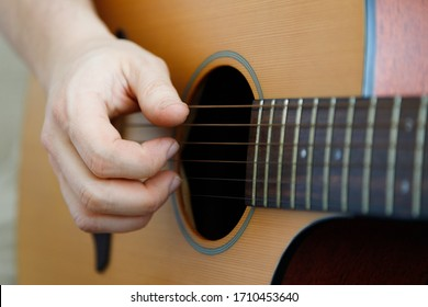 Close-up of a male hand playing a guitar. Learning music. Fun, live music.