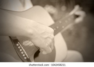 Close-up male hand playing on acoustic guitar outdoor. Vintage tone.