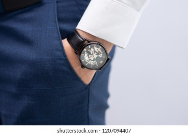 Close-up of male hand in pocket with modern elegant wristwatch. Caucasian businessman wearing stylish watch. Fashion and punctuality concept