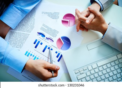 Close-up of male hand pointing at business document during discussion
