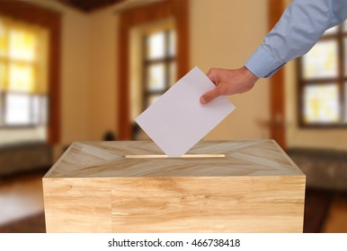 Close-up of male hand, putting voting paper into a ballot box, at a polling station