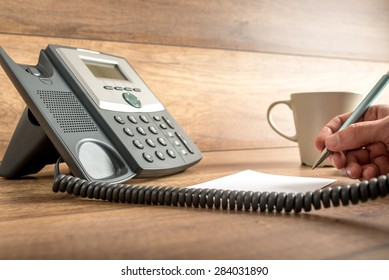 Closeup of male hand taking important notes as he answers a call on a classical landline telephone. Concept of assistance and secretary work.