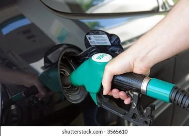 Closeup of male hand topping up car tank with unleaded 95 gasoline
